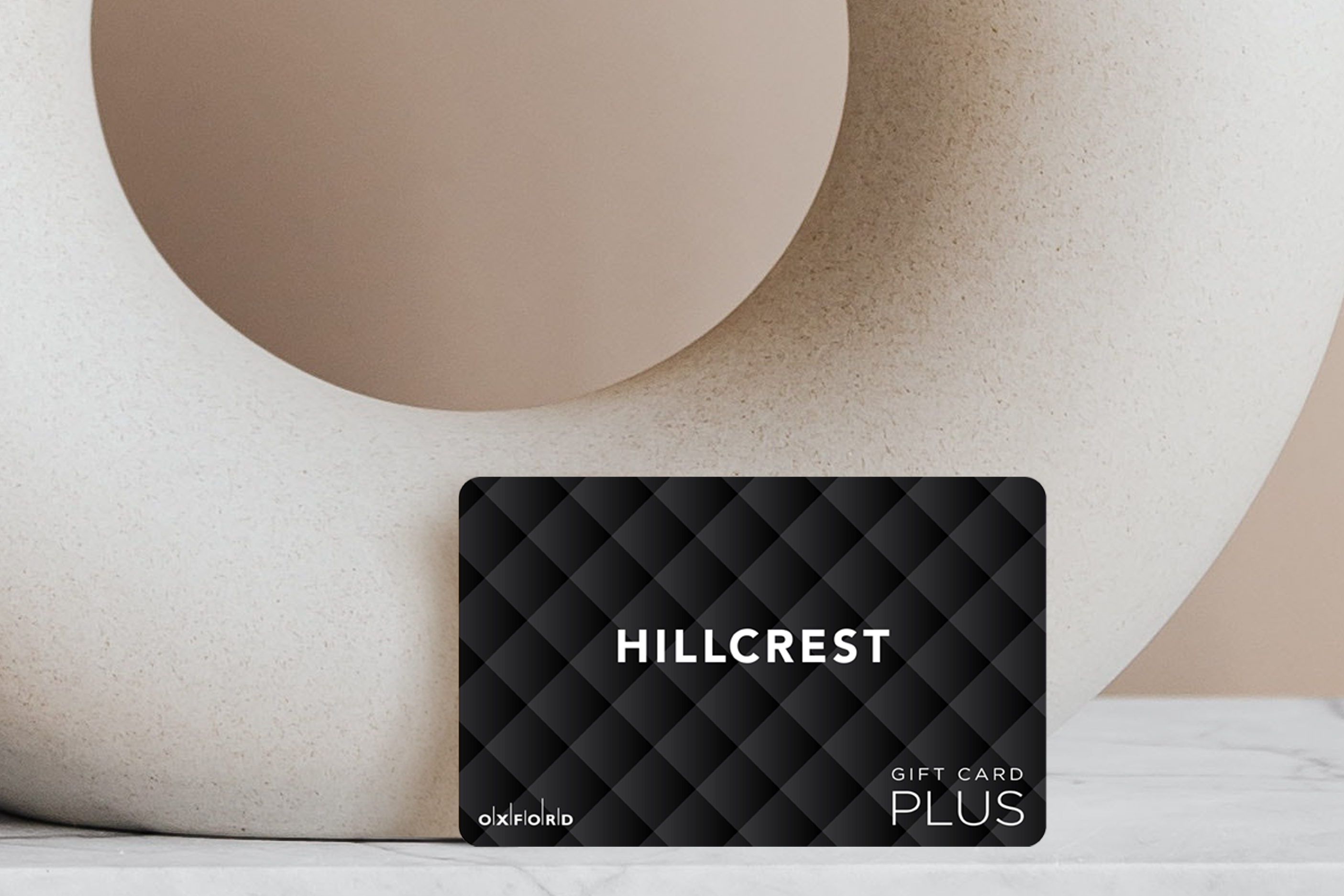 Hillcrest quilted gift card leaning against beige circular vase.