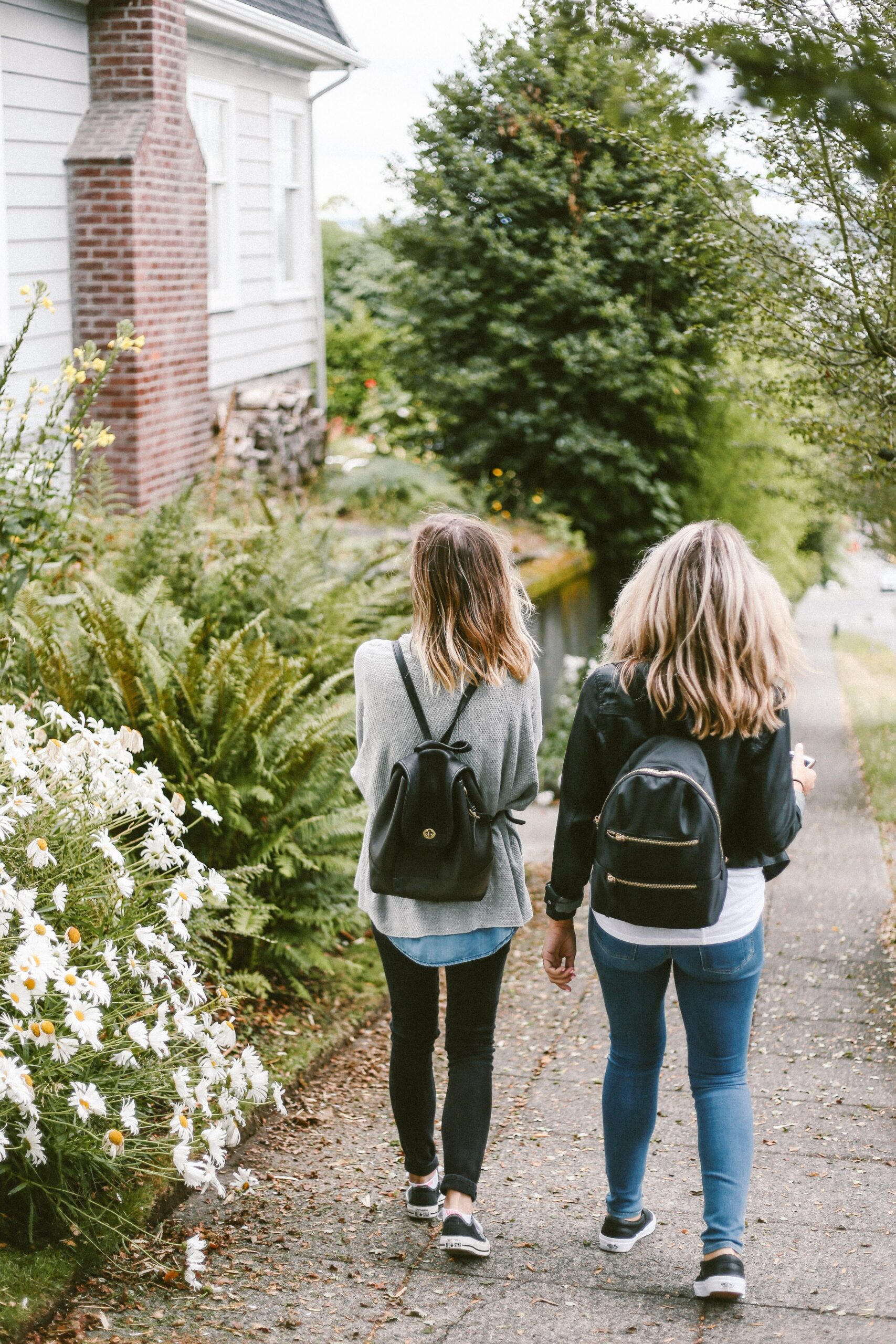 two girls with leather backpacks